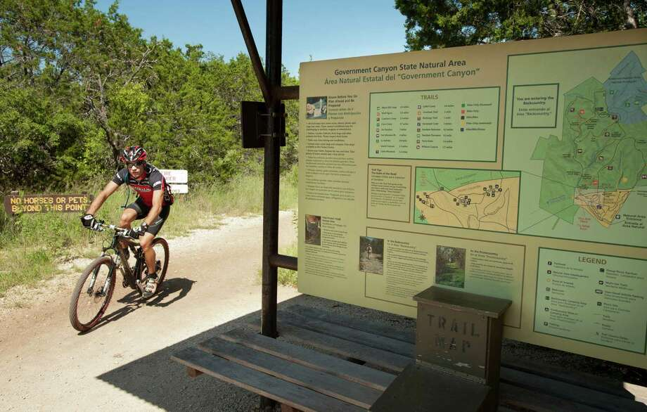 A cyclist rides by a map of park trails at the Joe Johnston trail head, Sunday, Sept. 23, 2012, at the Government Canyon State Natural Area in San Antonio. Photo: Darren Abate, Darren Abate/For The Express-New