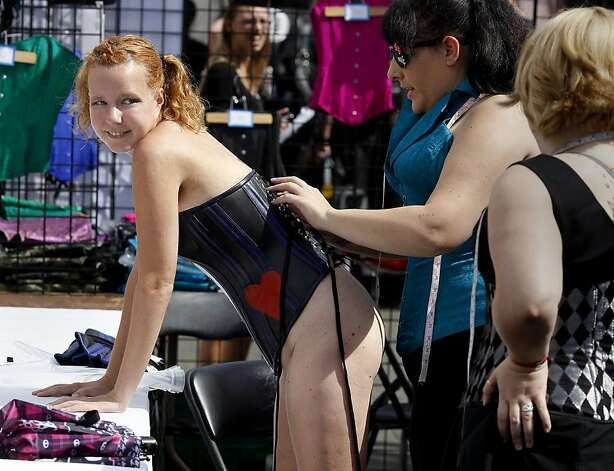 Jesse Kat (left) gets laced up in a corset at a busy shop on Folsom Street, which was teeming with decked-out fairgoers. Photo: Brant Ward, The Chronicle