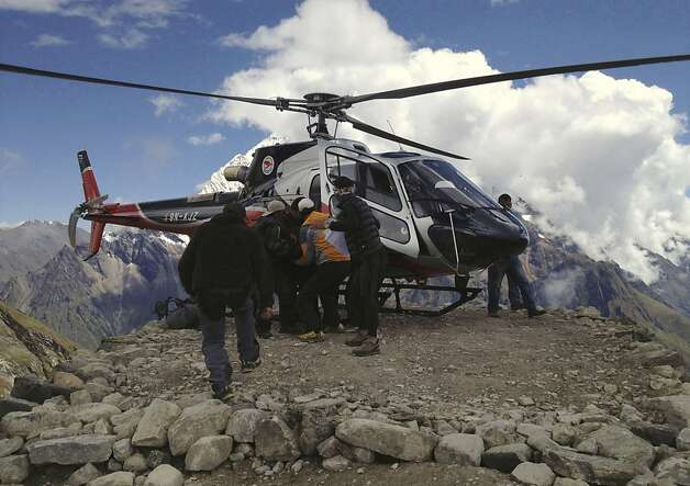 In this photo provided by Nepalese airline Simrik Air, an injured victim of an avalanche is carried to a helicopter after being rescued at the base camp of Mount Manaslu in northern Nepal, Sunday, Sept. 23, 2012. The avalanche swept away climbers on a Himalayan peak in Nepal on Sunday, leaving at least nine dead and six others missing, officials said. (AP Photo/Simrik Air) Photo: Associated Press