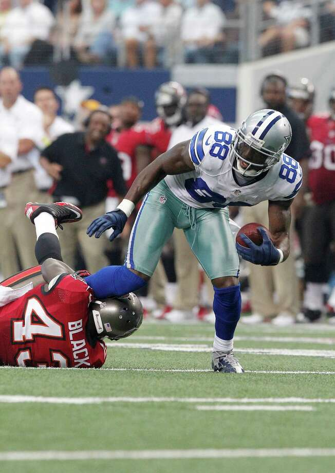 Dallas Cowboys wide receiver Dez Bryant (88) carries the ball as Tampa Bay Buccaneers free safety Ahmad Black (43) attempts to tackle during the second half of an NFL football game, Sunday, Sept. 23, 2012 in Arlington, Texas. (AP Photo/Tim Sharp) Photo: Tim Sharp, Associated Press / FR62992 AP