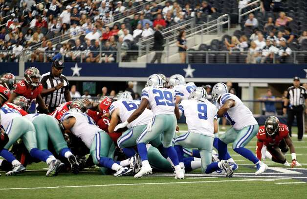 Dallas Cowboys' Tony Romo (9) takes a knee in a victory formation as the Tampa Bay Buccaneers rush the offense in the final seconds of an NFL football game Sunday, Sept. 23, 2012, in Arlington, Texas. (AP Photo/LM Otero) Photo: LM Otero, Associated Press / AP