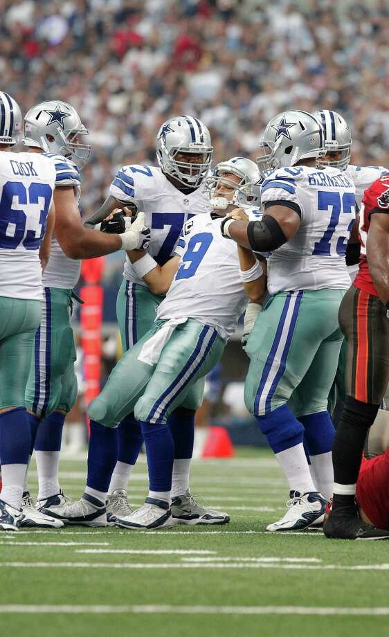 Dallas Cowboys quarterback Tony Romo (9) is helped to his feet by teammates during the second half of an NFL football game against the Tampa Bay Buccaneers, Sunday, Sept. 23, 2012 in Arlington, Texas. (AP Photo/Tim Sharp) Photo: Tim Sharp, Associated Press / FR62992 AP