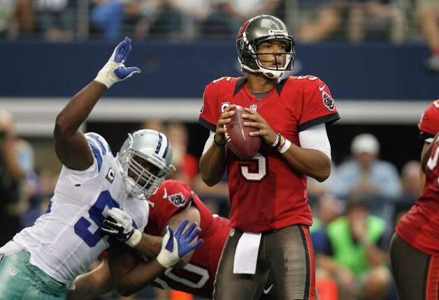 Tampa Bay Buccaneers quarterback Josh Freeman (5) looks to pass  Dallas Cowboys outside linebacker DeMarcus Ware (94) during the second half of an NFL football game against the Dallas Cowboys Sunday, Sept. 23, 2012 in Arlington, Texas. (AP Photo/LM Otero) Photo: LM Otero, Associated Press / AP