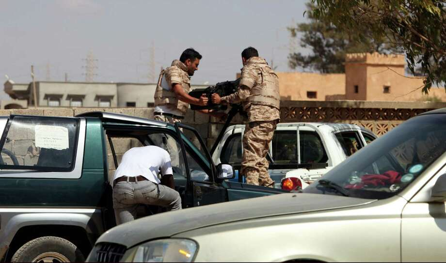 Soldiers from the Libyan National Army  get ready to enter  Rafallah al-sahati Islamic Militia Brigades compound, the compound buildings can be seen behind the wall, in Benghazi, Libya, Saturday, Sept. 22, 2012.  On Friday evening hundreds of protesters angry over last week's killing of the U.S. ambassador to Libya stormed the compound of the Islamic extremist Ansar al-Shariah Brigade militia suspected in the attack, evicting militiamen and setting fire to their building. After taking over the Ansar compound, protesters then drove to attack the Benghazi headquarters of Rafallah Sahati where militiamen opened fire on the protesters, who were largely unarmed leaving at least 20 wounded, and several killed according to hospital sources. (AP Photo/Mohammad Hannon) Photo: Mohammad Hannon