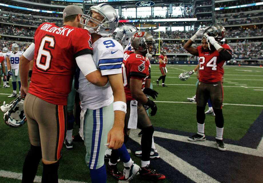 Tampa Bay Buccaneers quarterback Dan Orlovsky (6) and Dallas Cowboys quarterback Tony Romo (9) embrace after an NFL football game, Sunday, Sept. 23, 2012 in Arlington, Texas. The Cowboys won 16-10. (AP Photo/LM Otero) Photo: LM Otero, Associated Press / AP