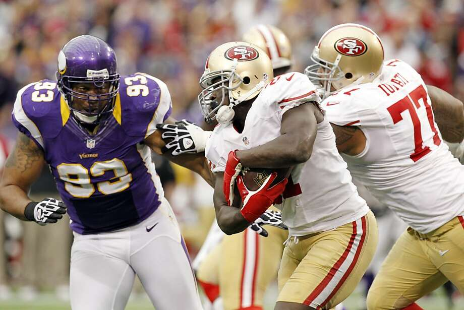 Frank Gore, pursued by Kevin Williams (93), got only 12 rushing attempts. Photo: Genevieve Ross, Associated Press