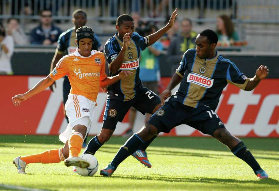 CHESTER, PA - SEPTEMBER 23: Calen Carr #3 of the Houston Dynamo gets the ball through the defending of Ramon Gaddis #28 and Amobi Okugo #14 of the Philadelphia Union at PPL Park on September 23, 2012 in Chester, Pennsylvania. Photo: Chris Gardner, Getty Images / 2012 Getty Images