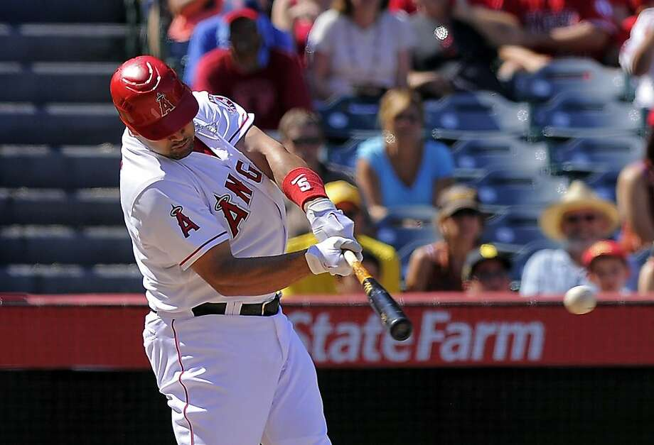 Albert Pujols, right, reached the 100-RBI mark for the 11th time in 12 big-league seasons with a two-run double as the Angels remained 2 1/2 games behind the A's for the second wild-card spot. Photo: Mark J. Terrill, Associated Press
