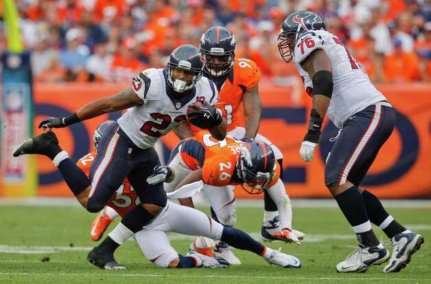 Houston Texans running back Arian Foster (23) tries to avoid a tackle by Denver Broncos defensive back Tony Carter (32) as Houston Texans tackle Duane Brown (76) looks on in the fourth quarter of an NFL football game Sunday, Sept. 23, 2012, in Denver. (AP Photo/David Zalubowski) Photo: David Zalubowski, Associated Press / AP
