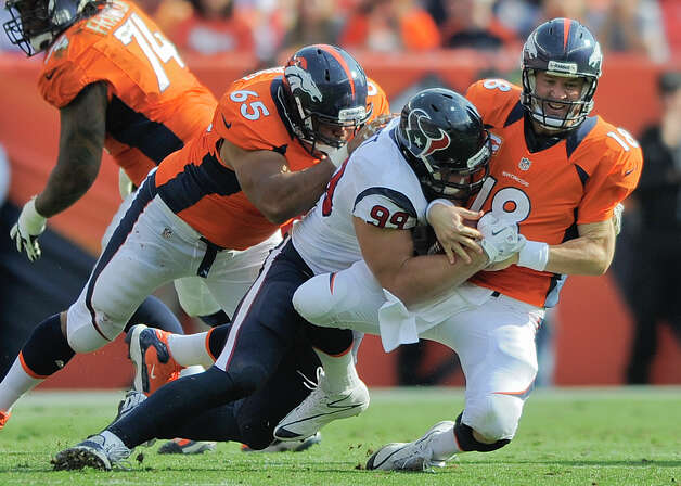Denver Broncos quarterback Peyton Manning (18) is sacked by Houston Texans defensive end J.J. Watt (99) as guard Manny Ramirez (65) defends in the third quarter of an NFL football game Sunday, Sept. 23, 2012, in Denver. (AP Photo/Jack Dempsey) Photo: Jack Dempsey, Associated Press / FR42408 AP