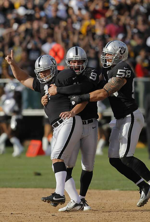 Sebastian Janikowski is congratulated by Shane Lechler, center, and Dave Tollefson, right, after Janikowski kicked the game winning field goal as time expired. The Oakland Raiders played the Pittsburgh Steelers at O.co Coliseum in Oakland, Calif., on Sunday, September 23, 2012, and defeated the Steelers 34-31. Photo: Carlos Avila Gonzalez - San Fran, The Chronicle