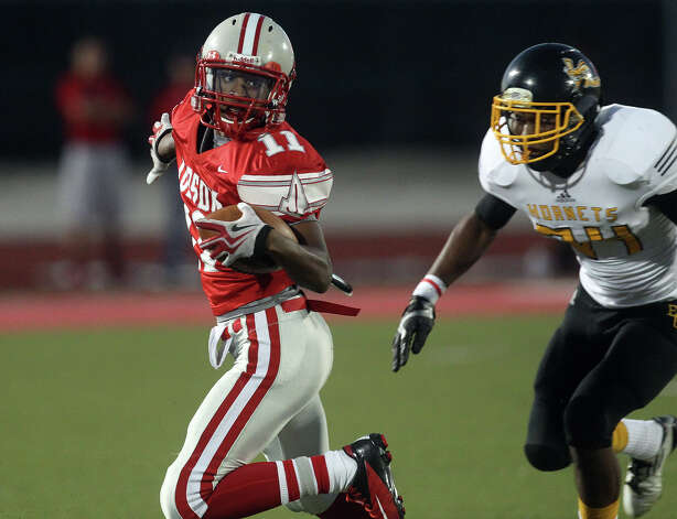 Judson's Andre Wilson (11) evades a tackle by East Central's David Clay (34) during their game at D.W. Rutledge Stadium on Friday, Sept. 21, 2012. Photo: Kin Man Hui, Express-News / ©2012 San Antonio Express-News