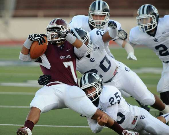 Receiver Henry Peralta (7) of Highlands is tackled by Steven Sanchez (25) and Leo Sanchez (20) of Central Catholic during high-school football action at Alamo Stadium on Thursday, Sept. 20, 2012. Photo: Billy Calzada, Express-News / © San Antonio Express-News