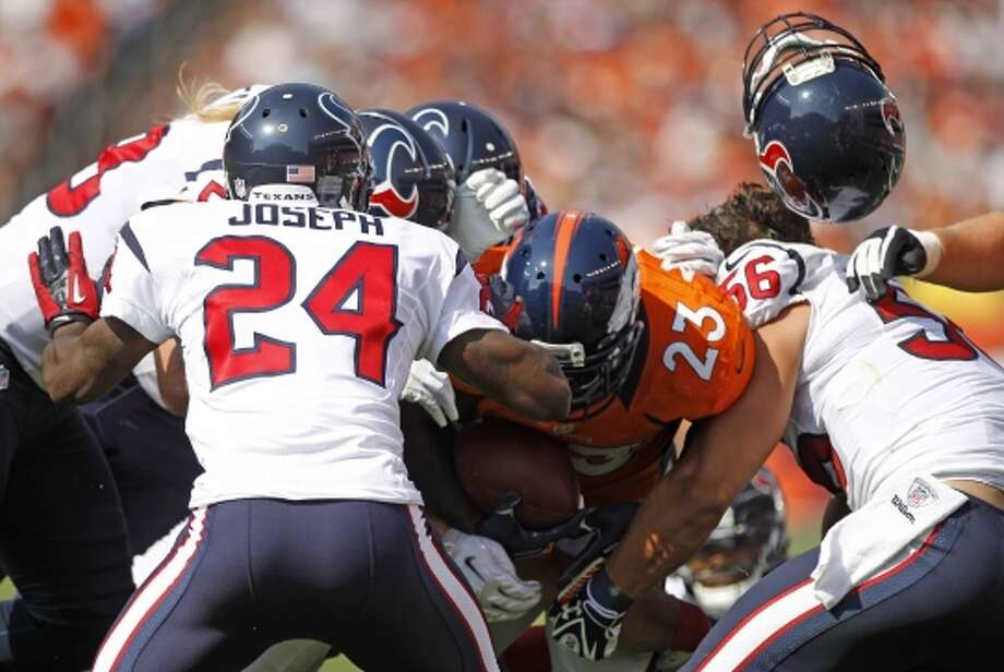 Texans inside linebacker Brian Cushing loses his helmet as he hits Broncos running back Willis McGahee with  cornerback Johnathan Joseph. (Brett Coomer / © 2012  Houston Chronicle)