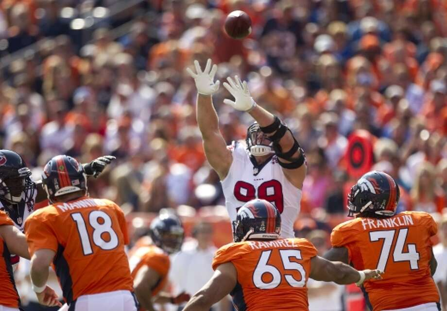 Houston Texans defensive end J.J. Watt leaps to try and block a pass by Denver Broncos quarterback Peyton Manning during the first quarter. (Brett Coomer / © 2012  Houston Chronicle)
