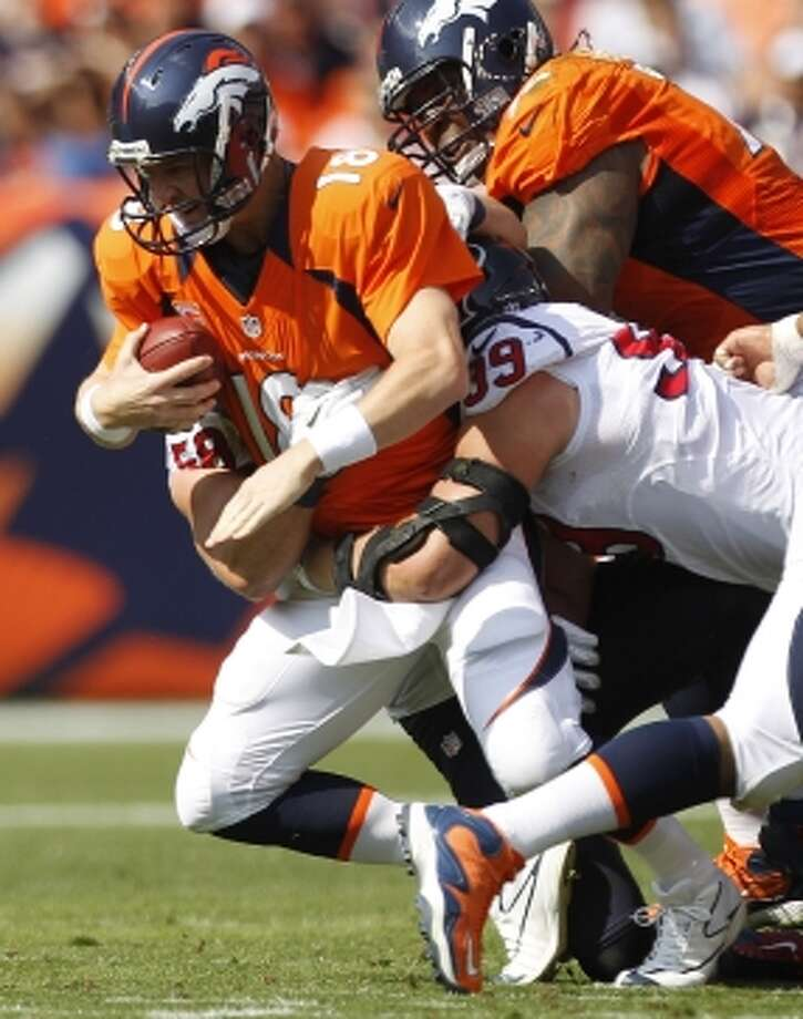 Texans defensive end J.J. Watt sacks Denver Broncos quarterback Peyton Manning during the first quarter at Sports Authority Field Sunday, Sept. 23, 2012, in Denver. (Brett Coomer / © 2012  Houston Chronicle)