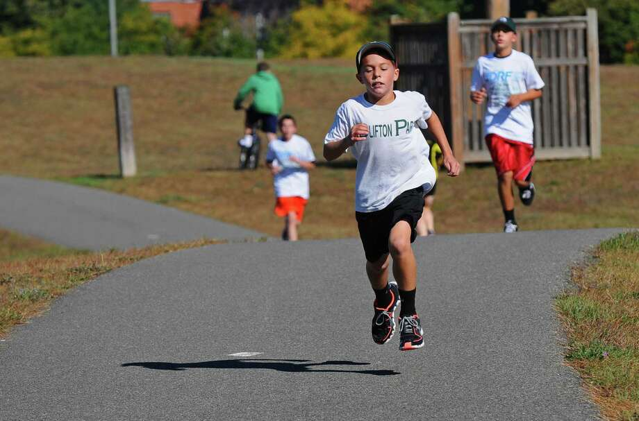 Joshua Szwarcberg of Ballston Lake, 9, powers his way to the win in the one mile children's run of the 3rd Annual 5k Run for JDRF (Juvenile Diabetes Research Foundation) at the Crossings of Colonie park, on Sunday Sept. 23, 2012 in Colonie, NY. His brother Jake, 12, right, came in second.  (Philip Kamrass / Times Union) Photo: Philip Kamrass / 00019367A