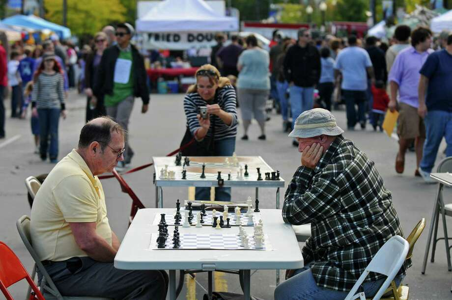 Brother John McManus, right, plays chess against Jim Lanpher, left, both of Albany, on a closed off Madison Avenue during the Upper Madison Street Fair on Sunday Sept. 23, 2012 in Albany, NY. Brother McManus is part of The Right Move, an organization that runs free scholastic chess tournaments, including their next one at Albany Academy on October 6, 2012. (Philip Kamrass / Times Union) Photo: Philip Kamrass / 00019368A