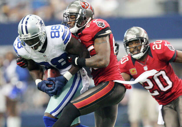 Dallas Cowboys' Dez Bryant is tackled by Tampa Bay Buccaneers' Aqib Talib as Ronde Barber comes up to help during the second half at Cowboys Stadium in Arlington, Texas, Sunday Sept. 23, 2012. The Cowboys won 16-10. Photo: Jerry Lara, Express-News / © 2012 San Antonio Express-News