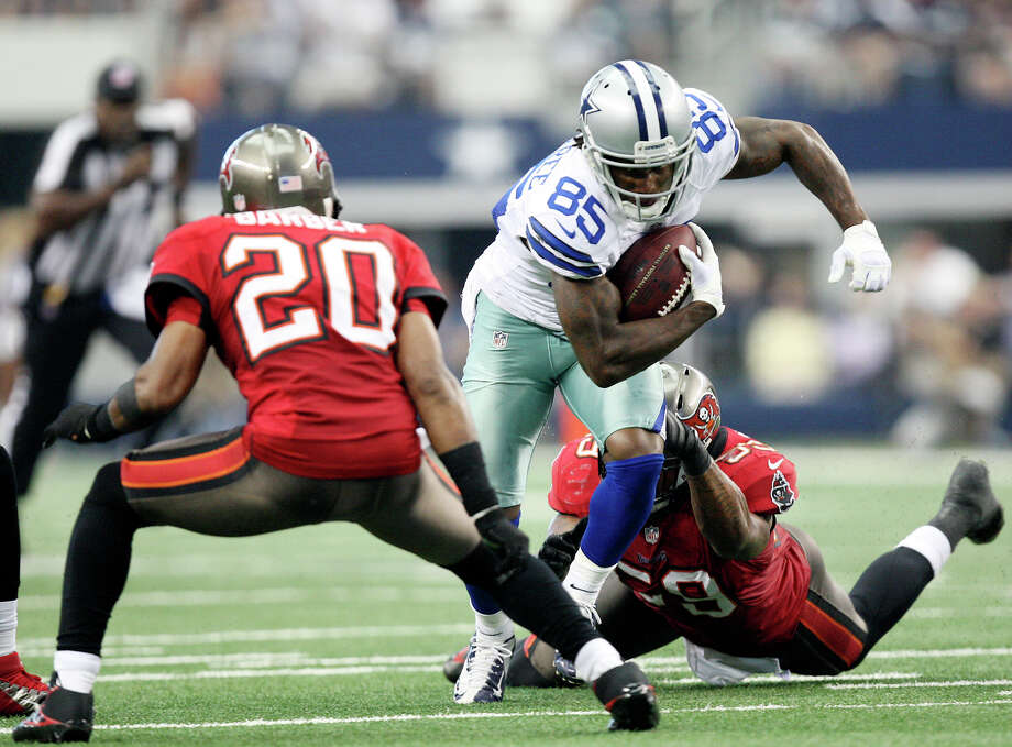 Dallas Cowboys's wide receiver Kevin Ogletree breaks a tackle by Tampa Bay Buccaneers' linebacker Mason Foster as defensive back Ronde Barber, left, come in to help during the second half at Cowboys Stadium in Arlington, Texas, Sunday Sept. 23, 2012. The Cowboys won 16-10. Photo: Jerry Lara, Express-News / © 2012 San Antonio Express-News