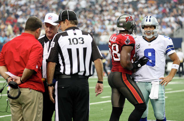 Dallas Cowboys's quarterback Tony Romo laughs with Tampa Bay Buccaneers' Quincy Black as Buccaneers Head Coach Greg Schiano, left, challeges the play during the third quarter at Cowboys Stadium in Arlington, Texas, Sunday Sept. 23, 2012. The Cowboys won 16-10. The play, called an incomplete pass, was challenged. It was ruled a fumble recovered by the Buccaneers. Photo: Jerry Lara, Express-News / © 2012 San Antonio Express-News