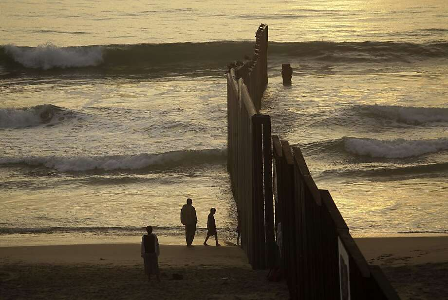 People hang out in the beach next to the border fence separating Mexico from the U.S. as the day comes to an end in Tijuana, Mexico, Saturday, Sept. 22, 2012.  (AP Photo/Dario Lopez-Mills) Photo: Dario Lopez-Mills, Associated Press