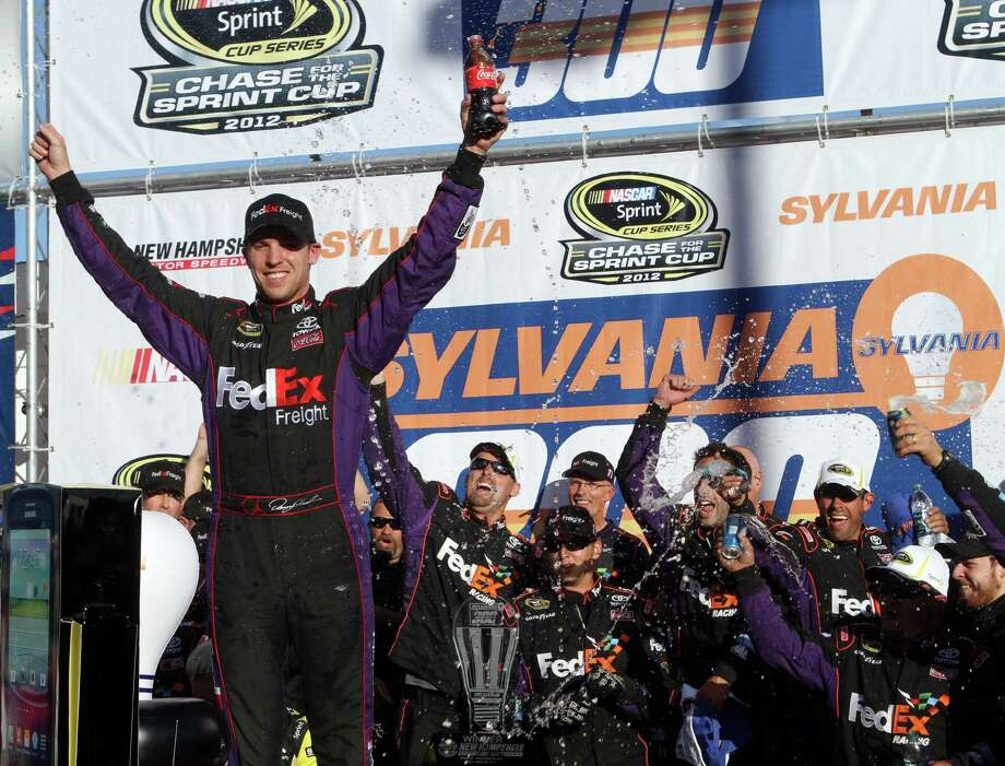 NASCAR driver Denny Hamlin celebrates with his team after winning the NASCAR Sprint Cup Series auto race at New Hampshire Motor Speedway, Sunday, Sept. 23, 2012, in Loudon, N.H. (AP Photo/Jim Cole) Photo: Jim Cole