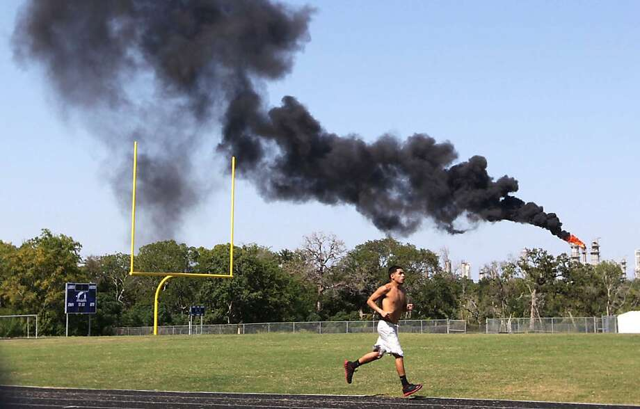 Joseph Gonzales, 18, runs laps at Chavez High School as he trains for a boxing tournament on Sunday, Sept. 23, 2012 in Houston. The thick black smoke from a local refinery can be seen in downtown Houston. (AP Photo/Houston Chronicle, Mayra Beltran) Photo: Mayra Beltran, Associated Press