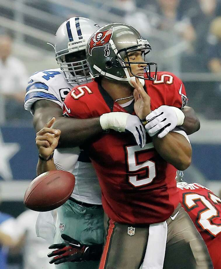 The Cowboys' DeMarcus Ware wraps up Buccaneers quarterback Josh Freeman and dislodges the ball all in one motion. Ware had two sacks in the game. Photo: Brandon Wade / Fort Worth Star-Telegram