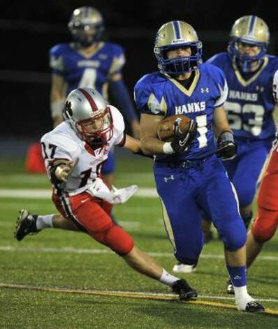 Newtown's Cooper Gold runs the ball while being tailed by Pomperaug's Carl Gatzendorfer during their game at Newtown High School on Friday, Sept. 21, 2012. Newtown won, 42-7. (Jason Rearick / Jason Rearick)