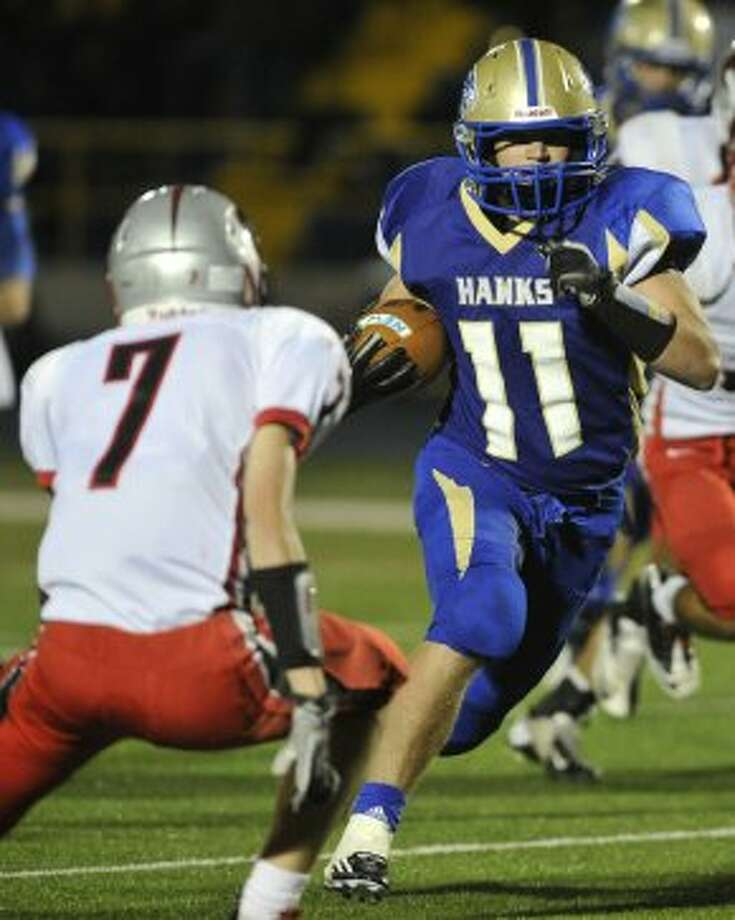 Newtown's Cooper Gold runs the ball while under pressure from Pomperaug's Samuel Rubinstein during their game at Newtown High School on Friday, Sept. 21, 2012. Newtown won, 42-7. (Jason Rearick / Jason Rearick)