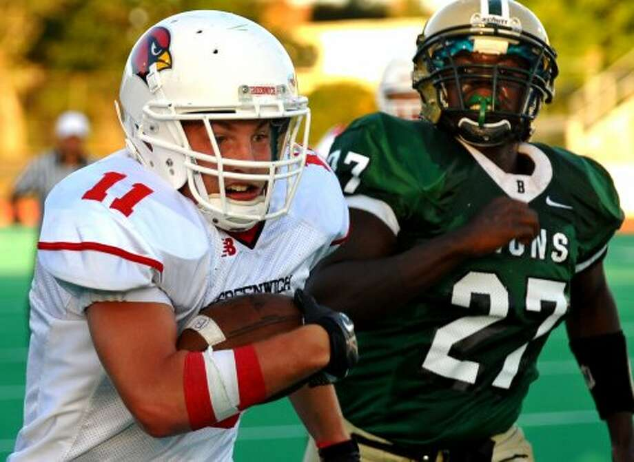 Greenwich's #11 Alex McMurray carries the ball as Bassick's #27 A.J. Brown looks to tackle, during football action in Bridgeport, Conn. on Friday September 21, 2012. (Christian Abraham / Christian Abraham)