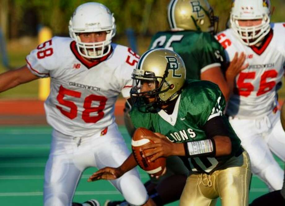 Bassick QB #10 Vochan Fowler looks for an opening to pass as Greenwich's #58 Alex McGee looks to sack him, during football action in Bridgeport, Conn. on Friday September 21, 2012. (Christian Abraham / Christian Abraham)