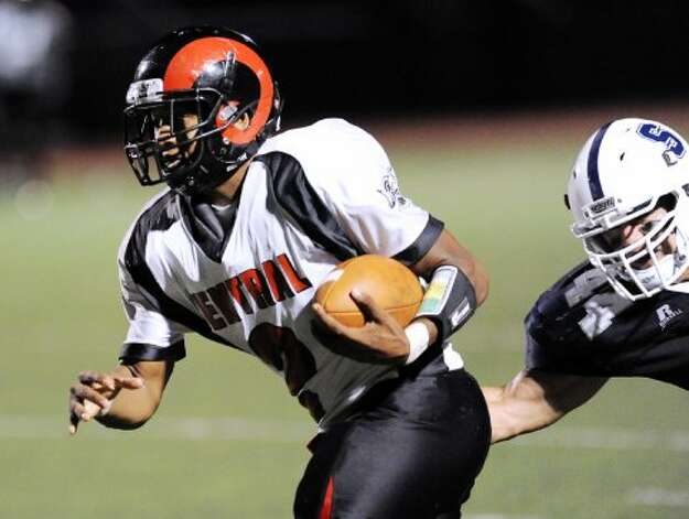 Bridgeport Central quarterback Xavier Hardison, left, # 2, heads upfield as Pieter Hoets # 44 of Staples attempts to tackle during the high school football game between Staples High School and Bridgeport Central High School at Staples in Westport, Friday night, Sept. 21, 2012. (Bob Luckey)