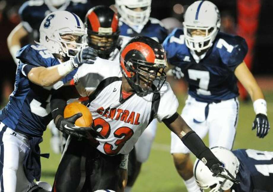 At center, Bridgeport Central running back Andrew Louis # 23 gets past Quinn Mendelson # 35 of Staples during high school football game between Staples High School and Bridgeport Central High School at Staples in Westport, Friday night, Sept. 21, 2012. In background at right is Lance Lonergan # 7 of Staples. (Bob Luckey)