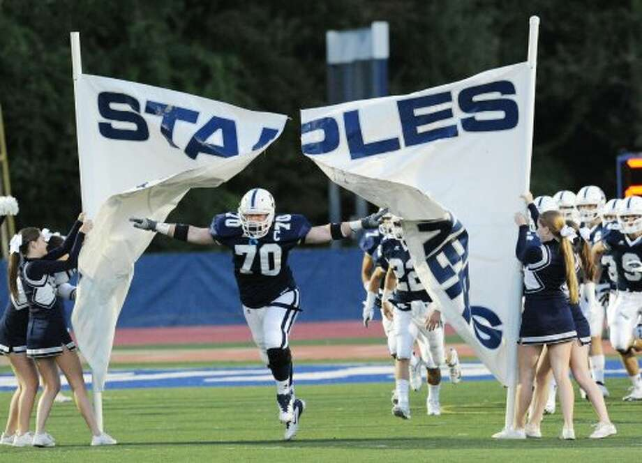 Captain, Kyle Vaughn, # 70 of Staples, leads the team onto the field during the high school football game between Staples High School and Bridgeport Central High School at Staples in Westport, Friday night, Sept. 21, 2012. (Bob Luckey)