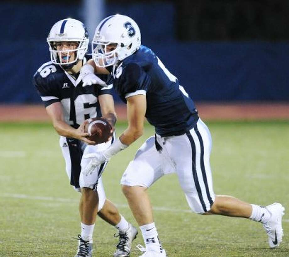 At left, Staples quarterback Jack Massie # 16 fakes the handoff to teammate Nicholas Kelly on route to a touchdown on a first quarter run during the high school football game between Staples High School and Bridgeport Central High School at Staples in Westport, Friday night, Sept. 21, 2012 (Bob Luckey)
