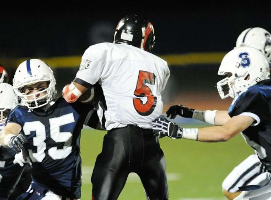 At left, Quinn Mendelson # 35 of Staples tackles Bridgeport Central's # 5 (not on roster) during the high school football game between Staples High School and Bridgeport Central High School at Staples in Westport, Friday night, Sept. 21, 2012. (Bob Luckey)