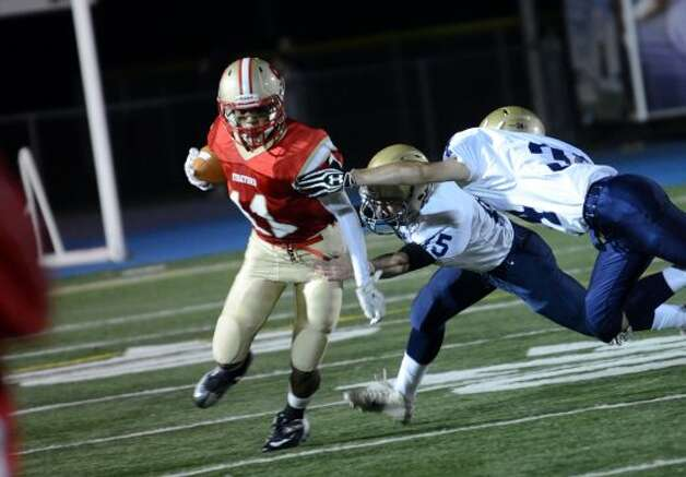 Stratford's Sergio Colon (11) carries the ball as Notre Dame Fairfield's Justin Bennett (15) and Logan Danville (34) defend during the football game at Bunnell High School in Stratford on Friday, Sept. 21, 2012. (Amy Mortensen)