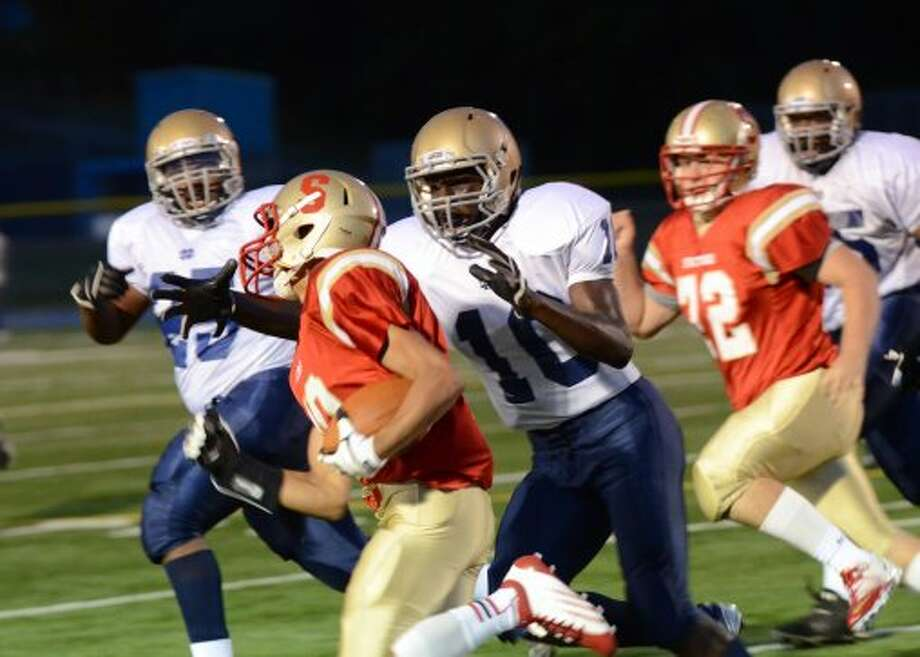 Stratford's Noah Provo (10) carries the ball as Notre Dame Fairfield's Carl Hoyt (10) defends during the football game at Bunnell High School in Stratford on Friday, Sept. 21, 2012. (Amy Mortensen)