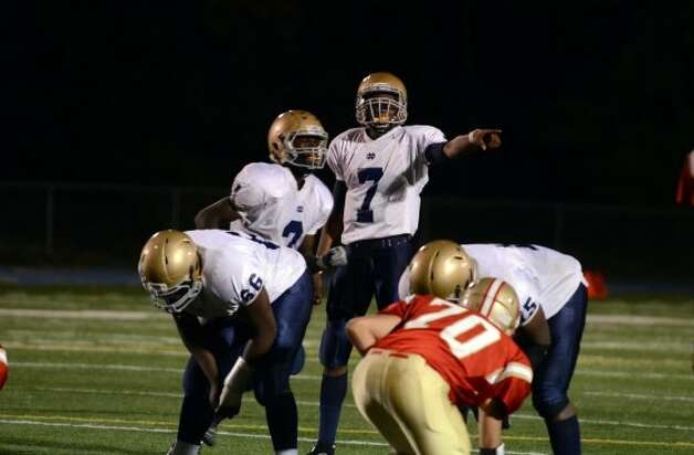 Notre Dame Fairfield's Glody Tumba (7) talks to a teammate during the football game against Stratford at Bunnell High School in Stratford on Friday, Sept. 21, 2012. (Amy Mortensen)