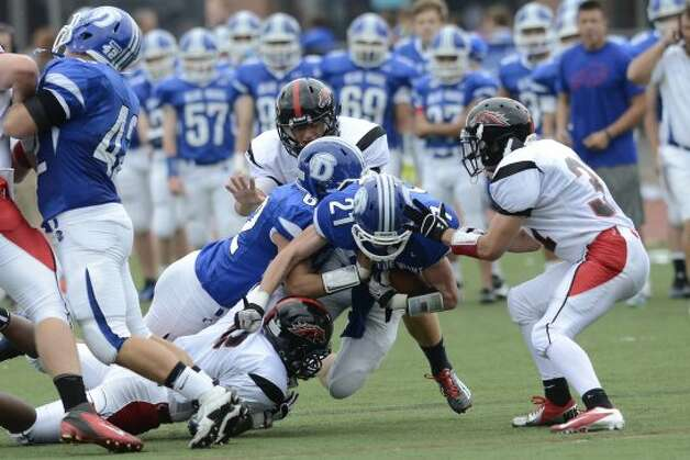 Darien's #21 Nicholas Lombardo encounters some resistance as Darien High School hosts Fairfield Warde High School in varsity football in Darien, CT on Sept. 22, 2012. (Shelley Cryan)