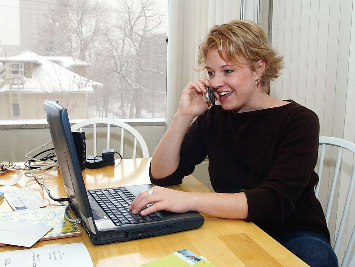 Emily O'Brien talks with a client on her cell phone as she works from her home on a snowy Wednesday, Feb. 11, 2004, in Denver.About 60,000 people have