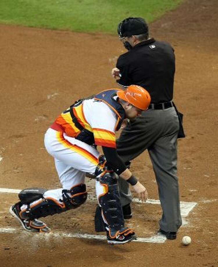 Astros catcher Chris Snyder has to look behind the home plate umpire Tim Timmons to find a passed ball during the first inning. (Nick de la Torre / © 2012 Houston Chronicle)