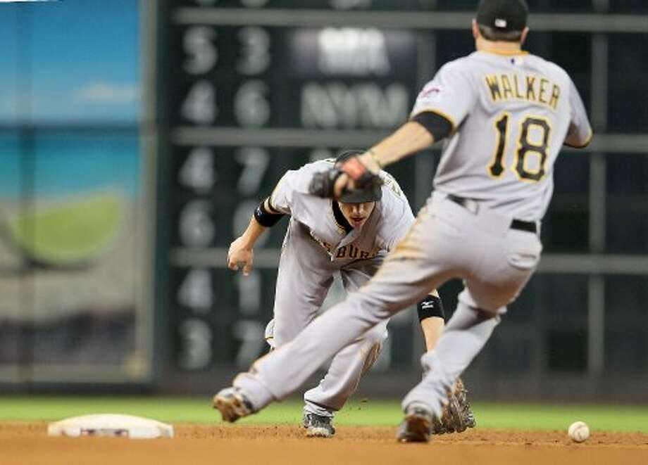 Pittsburgh Pirates shortstop Clint Barmes (12) makes an error as he reaches for a single hit by Houston Astros third baseman Matt Dominguez (30) during the seventh inning of an MLB baseball game at Minute Maid Park on Saturday, Sept. 22, 2012, in Houston.  ( Karen Warren / Houston Chronicle ) (Houston Chronicle)