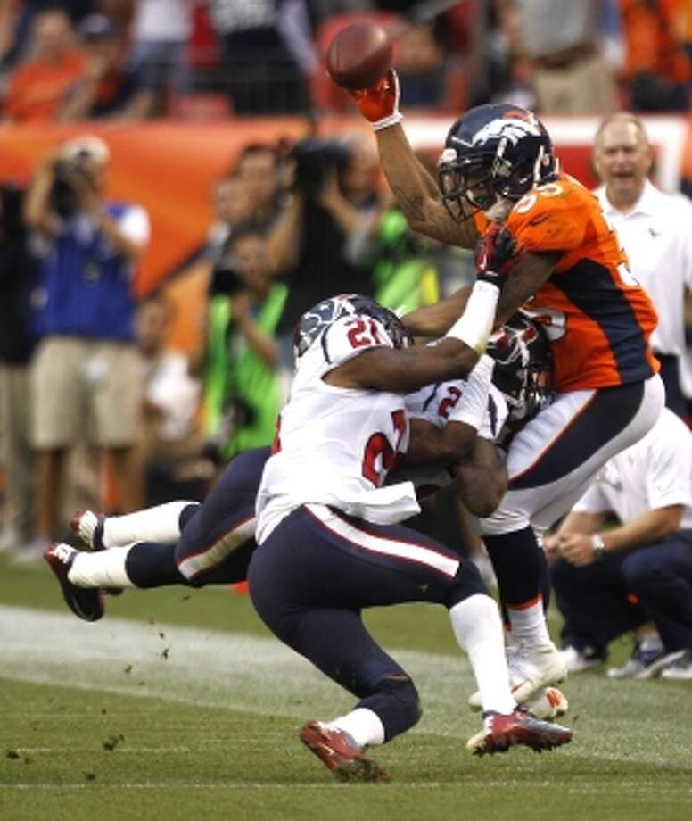 Broncos running back Lance Ball tries to lateral the football as he is hit by Texans defensive back Brice McCain on the final play of the game. (Brett Coomer / © 2012  Houston Chronicle)