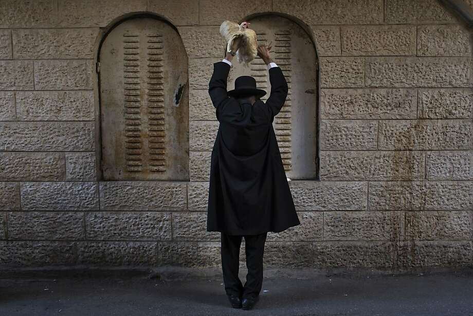 The sins of the feathered:An ultra-Orthodox Jewish man swings a 