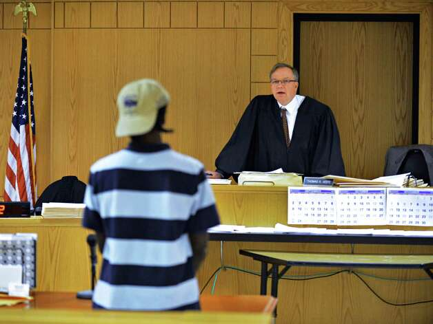 Albany City Court Judge Thomas Keefe speaks to a teenage defendant during his weekly youth court Tuesday afternoon Sept. 11, 2012.  He has a number of community organizations in the court and tries to treat these young offenders family-court style, even though the criminal age of responsibility in New York is 16.  (John Carl D'Annibale / Times Union) Photo: John Carl D'Annibale / 00019211A