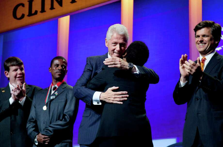 Former U.S. President Bill Clinton hugs Special Olympics athlete Loretta Claiborne after she addressed the opening session of the Clinton Global Initiative, Sunday, Sept. 23, 2012, in New York. From left are athletes Dustin Plunkett and Deon Namiseb. Tim Shriver, CEO of the Special Olympics, is at right. (AP Photo/Mark Lennihan) Photo: Mark Lennihan