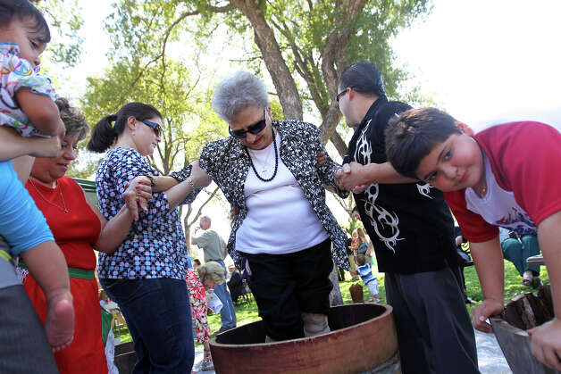 Rose Granieri, 86, stomps grapes with the assistance of her grandson, Jake Coleman, right, and Janice Hobbs, left, alongside Joseph Pirro, 7, during the 85th annual La Vendemmia Celebration at San Francesco di Paolo Catholic Church, September 23, 2012. Photo: JENNIFER WHITNEY / © Jennifer Whitney